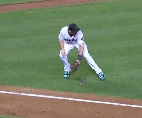 Bird appears under Arizona Diamondbacks fielder's glove after bunt