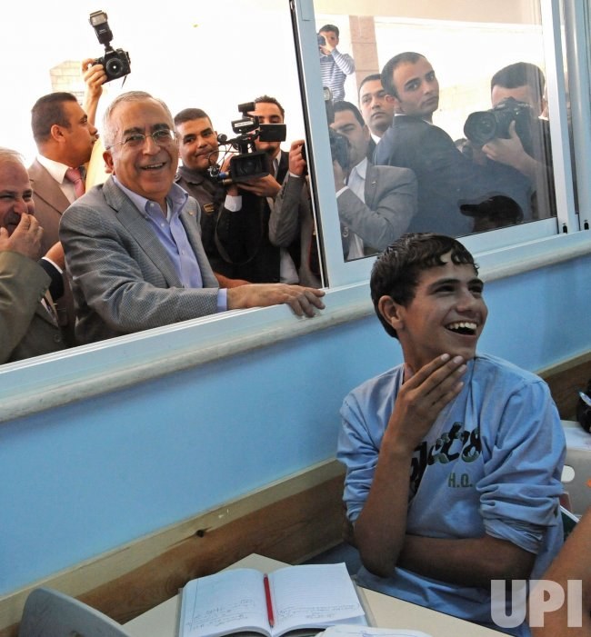 Palestinian Prime Minister Salam Fayyad greets students during the inauguration of a new school wing in East Jerusalem