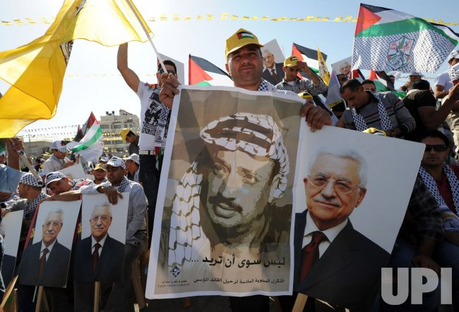 Palestinians hold posters of Palestinian President Mahmoud Abbas and Yasser Arafat at a rally to support Fatah and commemorate the sixth anniversary of Yasser Arafat's death