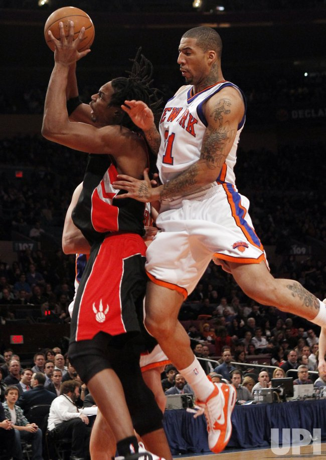 Toronto Raptors Chris Bosh is pushed from behind by New York Knicks Wilson Chandler at Madison Square Garden in New York