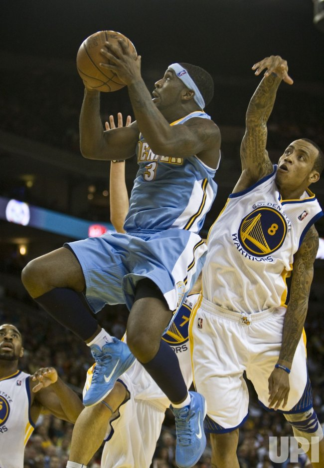 Warriors Monta Ellis tries to block Nuggets Ty Lawson in Oakland, California