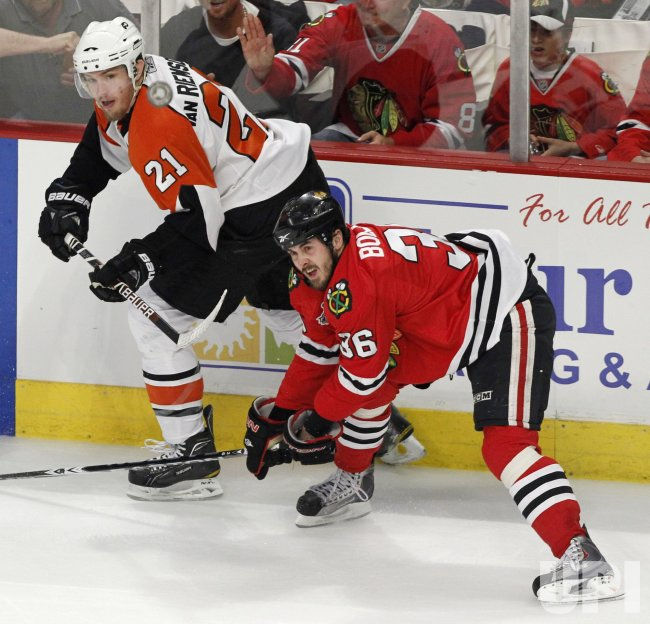 Flyers Riemsdyk and Blackhawks Bolland go for puck during the 2010 Stanley Cup Final