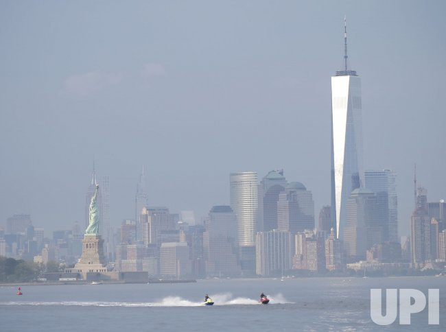 People Ride Jet Skis in the Hudson River with a view of the Statue of Liberty
