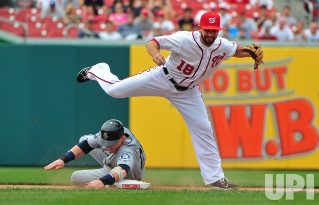 Nationals' Danny Espinosa steps over Seattle Mariners' Mike Carp in Washington