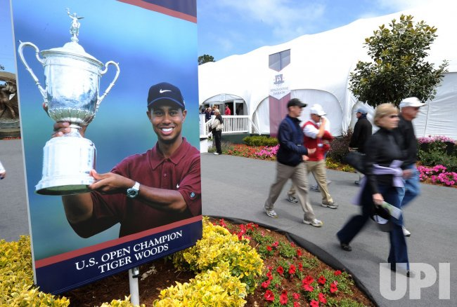 Fans walk past a poster of Tiger Woods during the U.S. Open in Pebble Beach, California