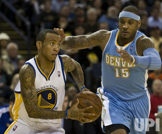 Warriors Monta Ellis drives past Nuggets Carmelo Anthony in Oakland, California