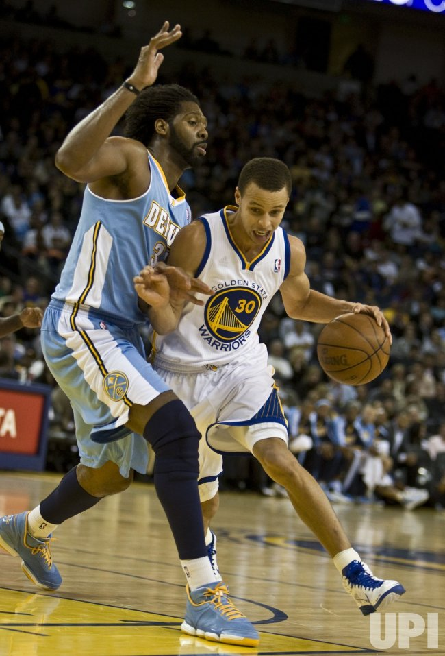 Warriors Stephen Curry drives on Denver Nuggets Nene in Oakland, California
