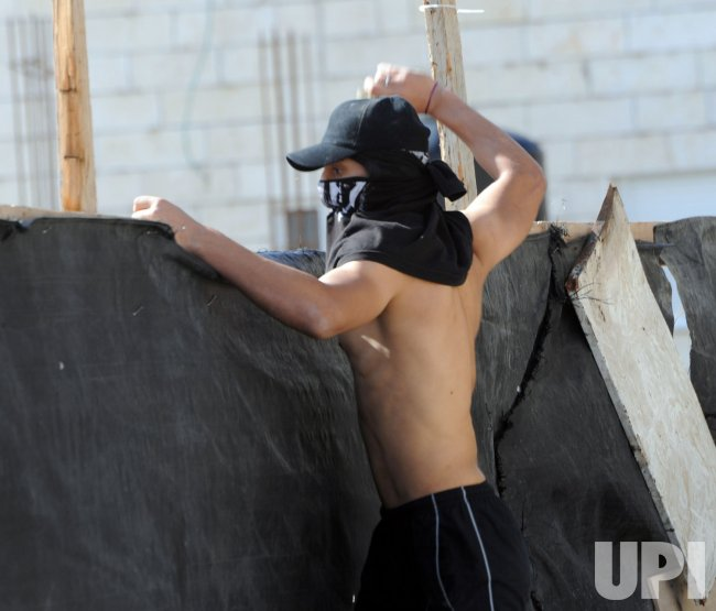 A Palestinian throws stones at Israeli forces in east Jerusalem