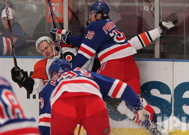 Philadelphia Flyers Lukas Krajicek gets pushed into the boards by New York Rangers P.A. Parenteau at Madison Square Garden in New York