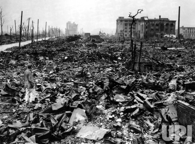AN UNIDENTIFIED NEWSMAN STANDS AMID THE RUBBLE OF HIROSHIMA IS SEPTEMBER 1945