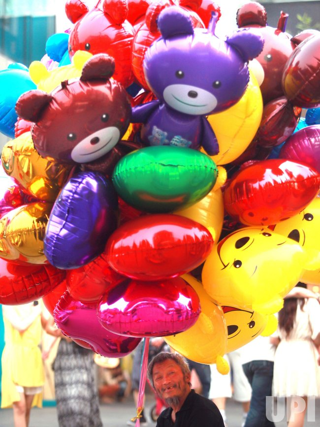 A Chinese migrant worker sells balloons in Beijing
