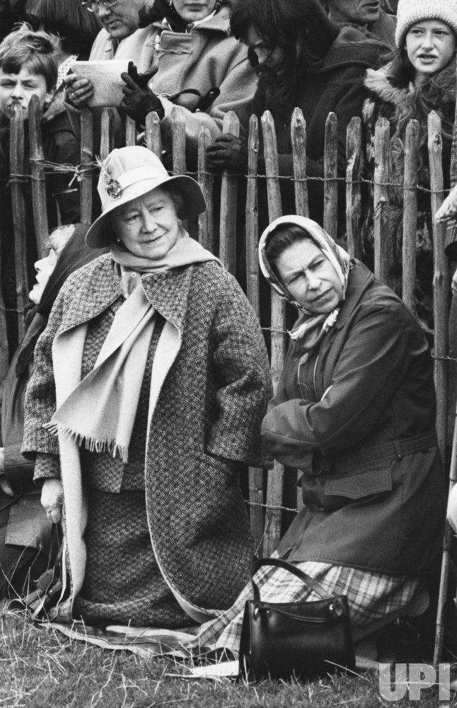 The Queen Mother Elizabeth and Queen Elizabeth II watch horse trials in kneeled positions