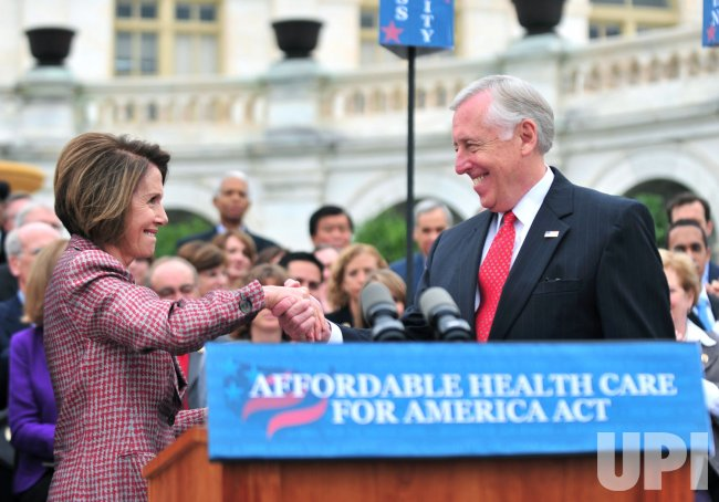 Speaker Pelosi shakes hands with Leader Hoyer during an event onhealth care reform in Washington