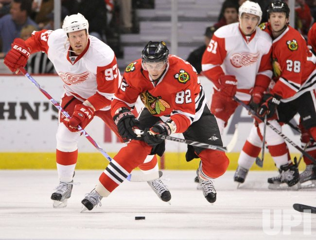 Blackhawks Kopecky and Red Wings Franzen skate after puck in Chicago
