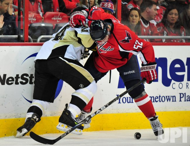 Washington Capitals' Mike Green and Pittsburgh Penguins' Matt Cooke fight for the puck in Washington