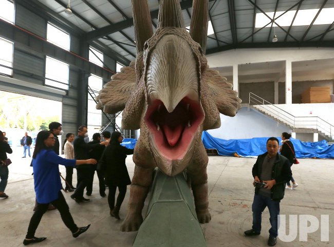A Chinese technician remotely controls a robotic dinosaur in Zigong, China