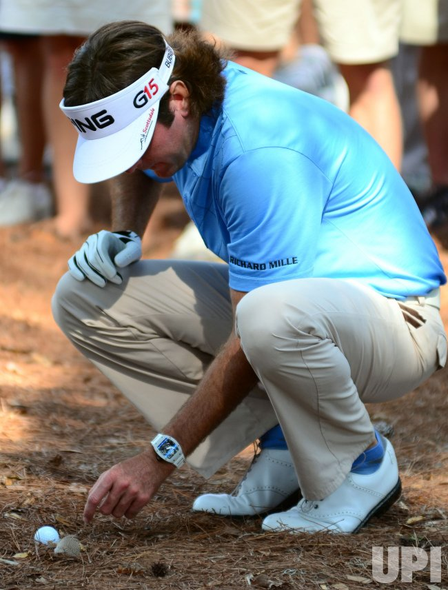 Bubba Watson moves debris during the TPC Players in Florida