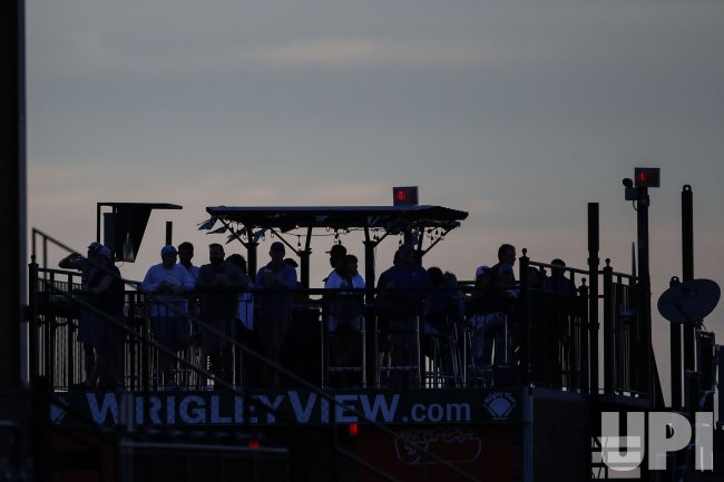 Fans watch from the Wrigley Rooftops a baseball game in Chicago