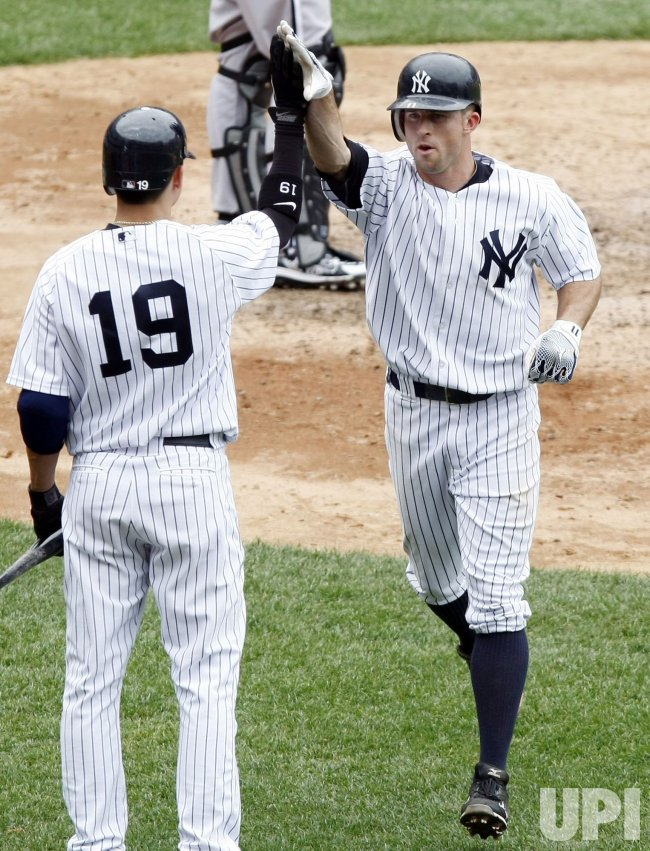 New York Yankees Ramiro Pena (19) slaps hands with Brett Gardner at Yankee Stadium in New York