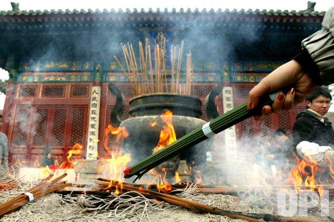 CHINESE LIGHT INCENSE STICKS AND PRAY AT TEMPLE - UPI com