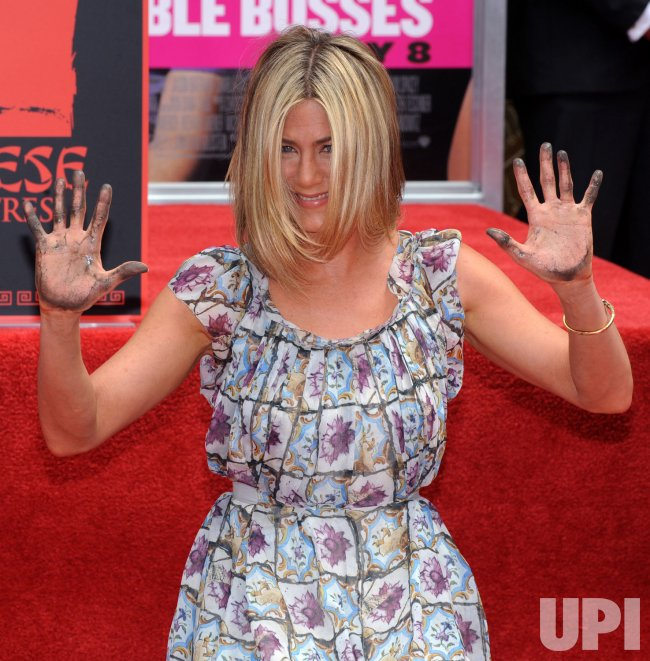 Jennifer Aniston raises her cement-covered hands during a ceremony at Grauman's in Los Angeles