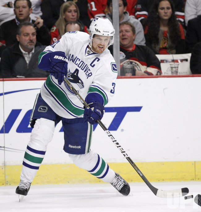Canucks Sedin passes against Blackhawks in Chicago
