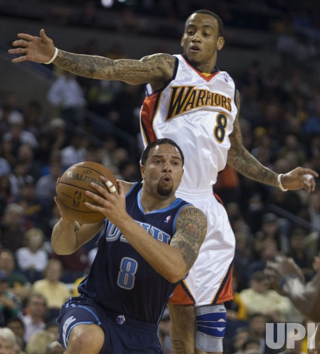 Utah Jazz Deron Williams slips under a leaping Golden State Warriors Monta Ellis in Oakland, California