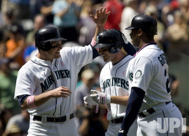 Seattle Mariners' Josh Wilson (C) is met at home plate by Ryan Langerhans (L) and Ken Griffey Jr., (R).