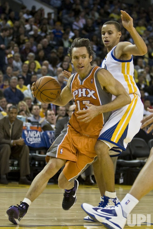 Phoenix Suns Steve Nash drives around Golden State Warriors Stephen Curry in Oakland, California