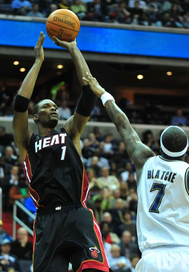 Miami Heat's Chris Bosh shoots over Washington Wizards' Andray Blatche in Washington