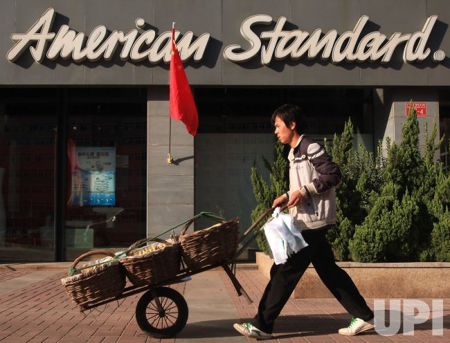 A Chinese vendor walks past an \'American Standard\' showroom in ...