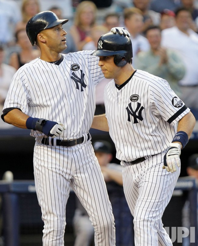 New York Yankees Dertek Jeter puts his hand on the helmet of Mark Teixeira at Yankee Stadium in New York