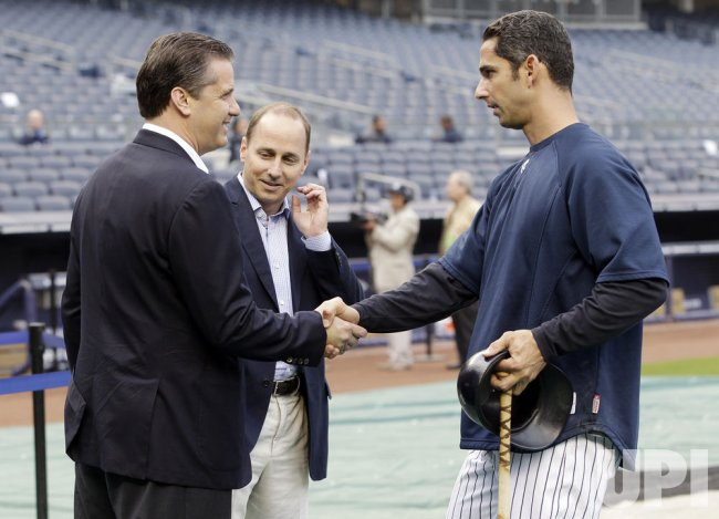 New York Yankees GM Brian Cashman watches Jorge Posada shake hands with NCAA Kentucky head coach John Calipari at Yankee Stadium in New York