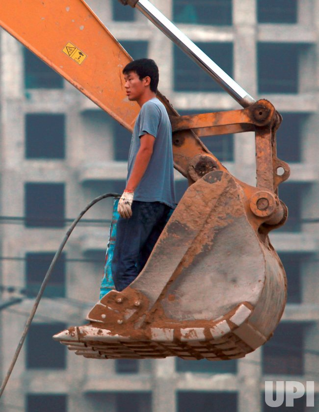 Chinese man stands in an excavator's shovel in Beijing