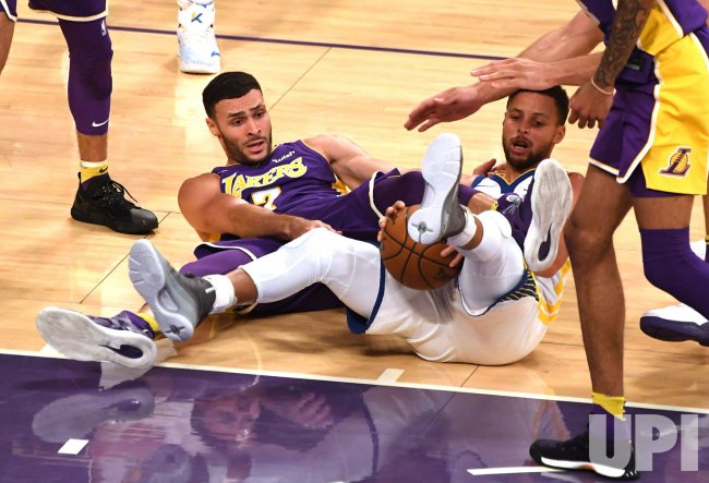 Lakers Larry Nance Jr (L) and Warriors Stephen Curry fight for ball in Los Angeles