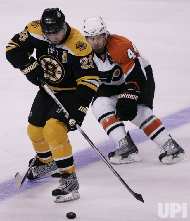 Bruins Recchi and Flyers Timonen chase puck in Game 7 of the NHL Eastern Conference Semi-Final in Boston, MA.