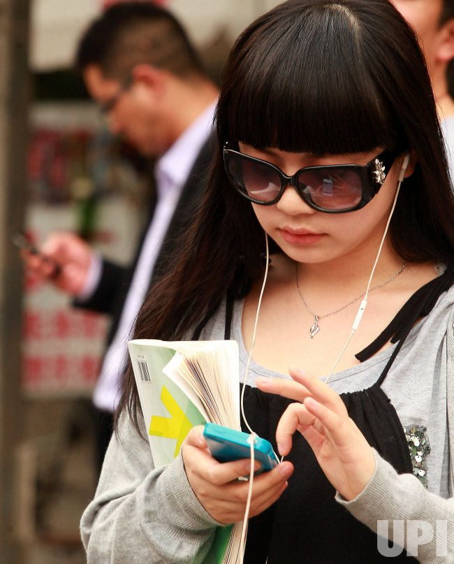 Chinese use their smart phones in downtown Beijing