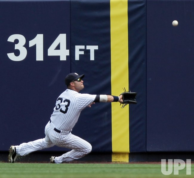 New York Yankees Nick Swisher makes a sliding catch at Yankee Stadium in New York