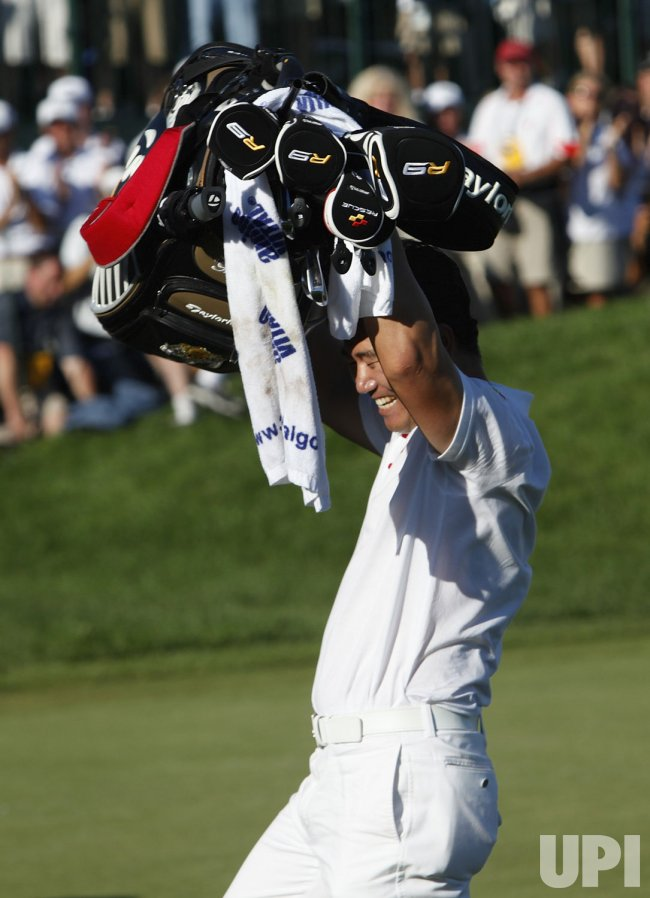 Y. E. Yang hoists his golf bag over his head after winning the 91st PGA Championship in Chaska, Minnesota