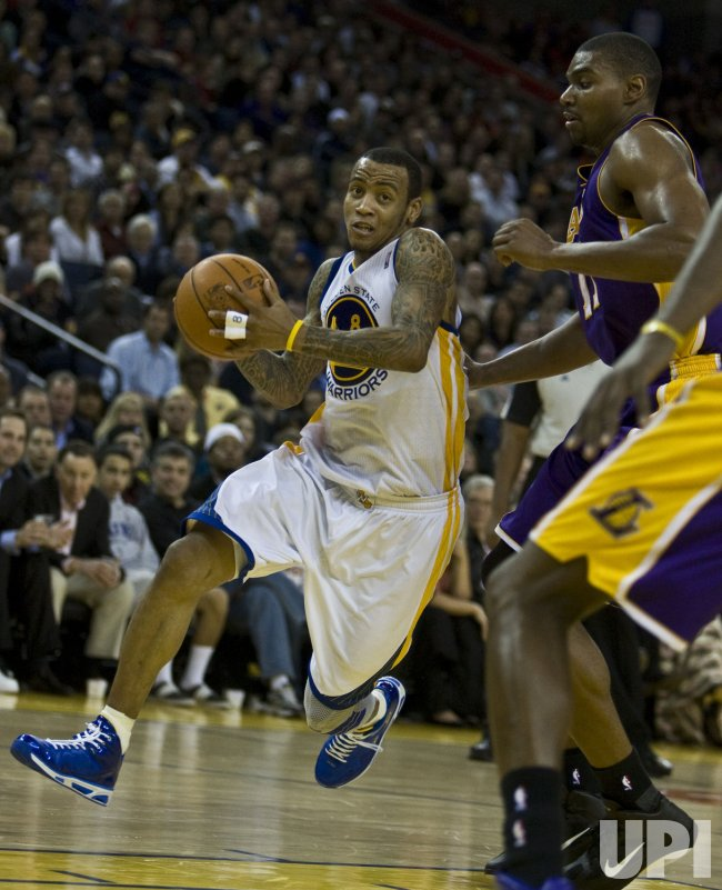 Golden State Warriors Monta Ellis drives on Los Angeles Lakers Andrew Bynum in Oakland, California