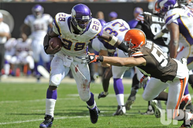 Minnesota Vikings running back Adrian Peterson runs past Cleveland Browns linebacker Eric Barton