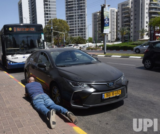 An Israeli Takes Cover As A Siren Alerts Of Rockets Fired From Gaza
