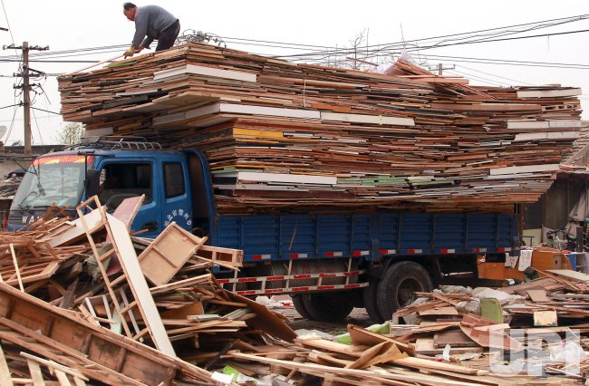 Chinese men load a truck with recyclable materials in Beijing
