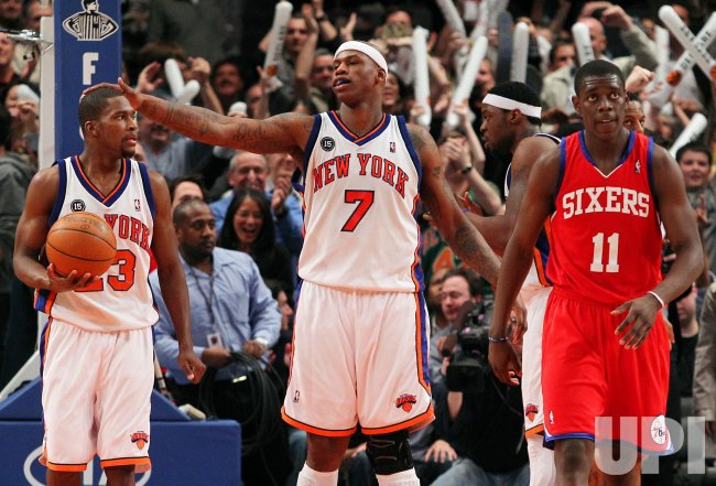New York Knicks Toney Douglas (23), Al Harrington and Philadelphia 76ers Jrue Holiday (11) react at Madison Square Garden