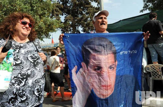 An Israeli man holds a banner of captured Israeli soldier Gilad Shalit outside a protest tent in Jerusalem