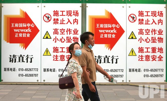 Chinese Walk Past Construction Site in Beijing, China