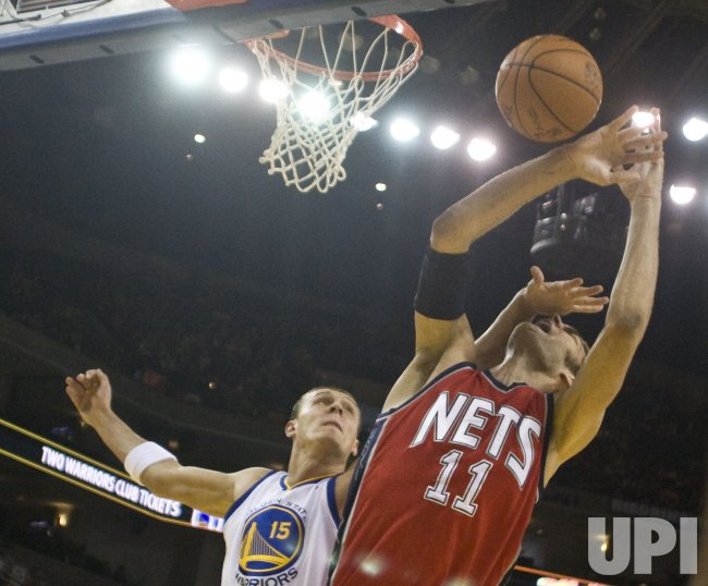 Nets Brook Lopez is fouled by Warriors Andris Biedrinsin Oakland, California