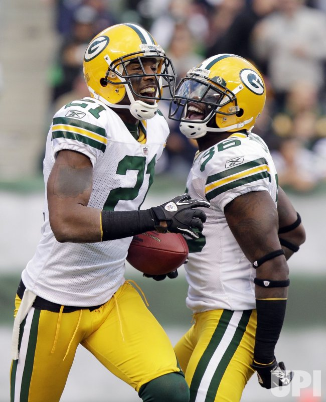 Green Bay Packers Charles Woodson and Nick Collins react after Woodson makes an interception at New Meadowlands Stadium in New Jersey
