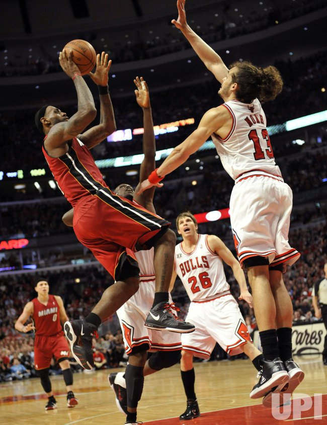 Heat's James shoots over Bulls' Noah in Chicago
