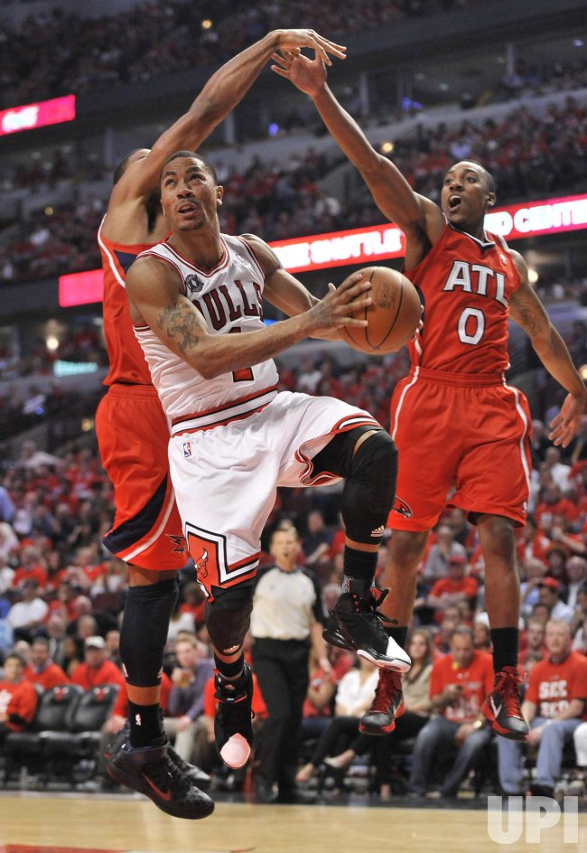 Bulls Rose drives past Hawks Horford and Teague in Chicago